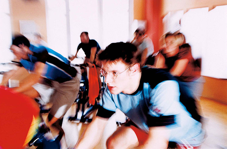 Gruppe in einem Fitnessstudio beim Spinning-Training.